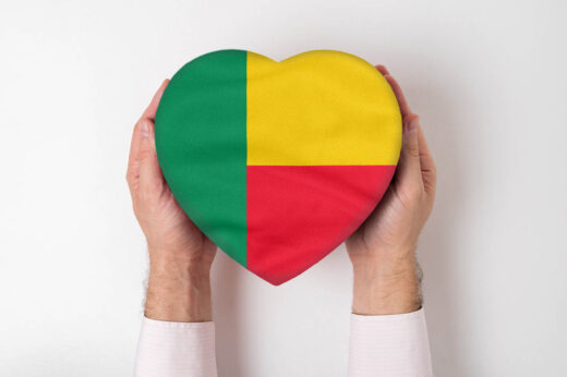 Flag Of Benin On A Heart Shaped Box In A Male Hands. White Background